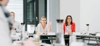 Zwei Frauen und ein Mann sitzen während eines Kurses an einem Tisch, die Frau in der Mitte meldet sich mit erhobener Hand.