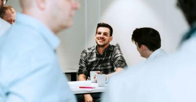 Studierender sitzt lachend mit seinem Kaffee am Tisch