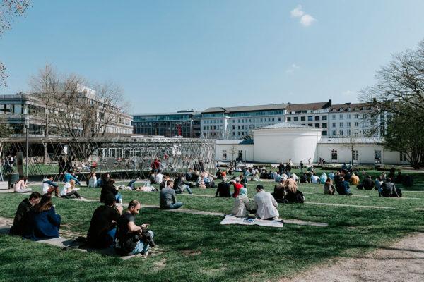 Menschen sitzen im Aachener Elisengarten