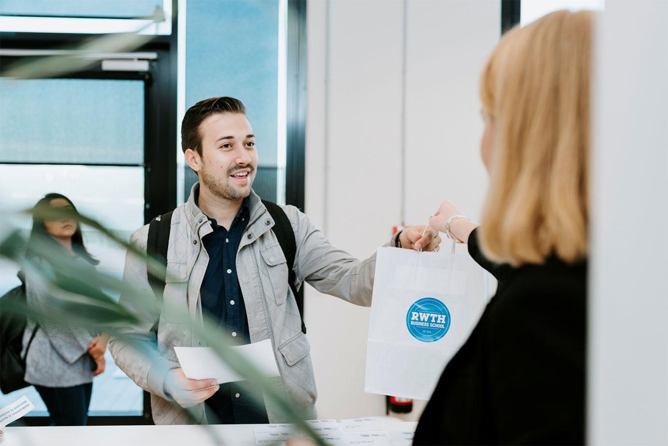 Mitarbeiterin überreicht Welcome Paket an Studierenden