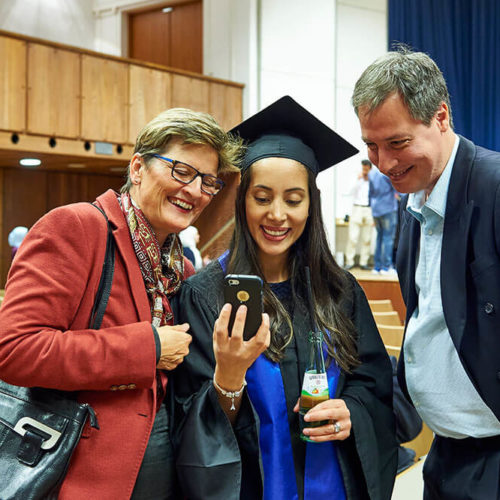 Student at graduation taking a selfie with her parents