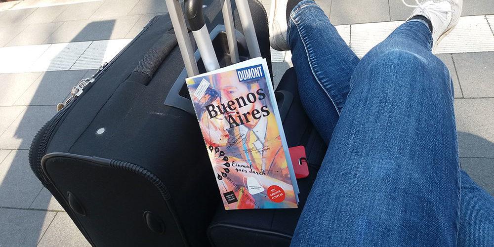 Person am Bahnsteig mit Koffern und Reiseführer über Buenos Aires