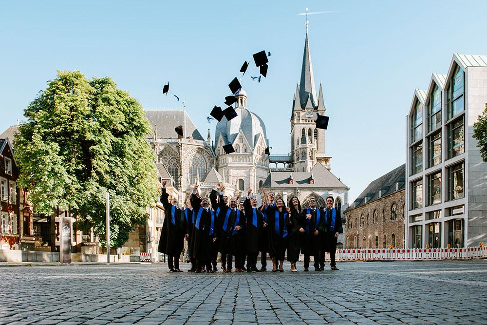 Gruppe von 12 Absolventen wirft ihre Hüte vor dem Aachener Dom