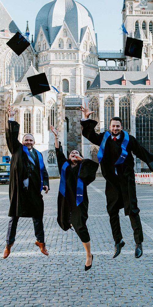3 Absolventen werfen nach ihrer Graduierung vor dem Aachener Dom ihre Hüte