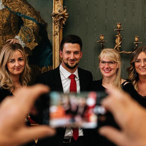 Absolvent des Executive MBA wird mit 3 Frauen gemeinsam mit dem Handy fotografiert