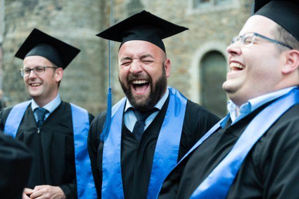 Absolventen bei Graduierungsfeier, lachend, im Talar