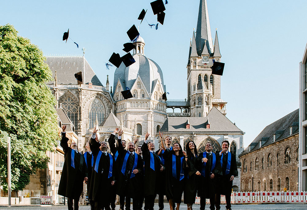 Studierende des Executive MBA beim Hüte werfen vor dem Aachener Dom