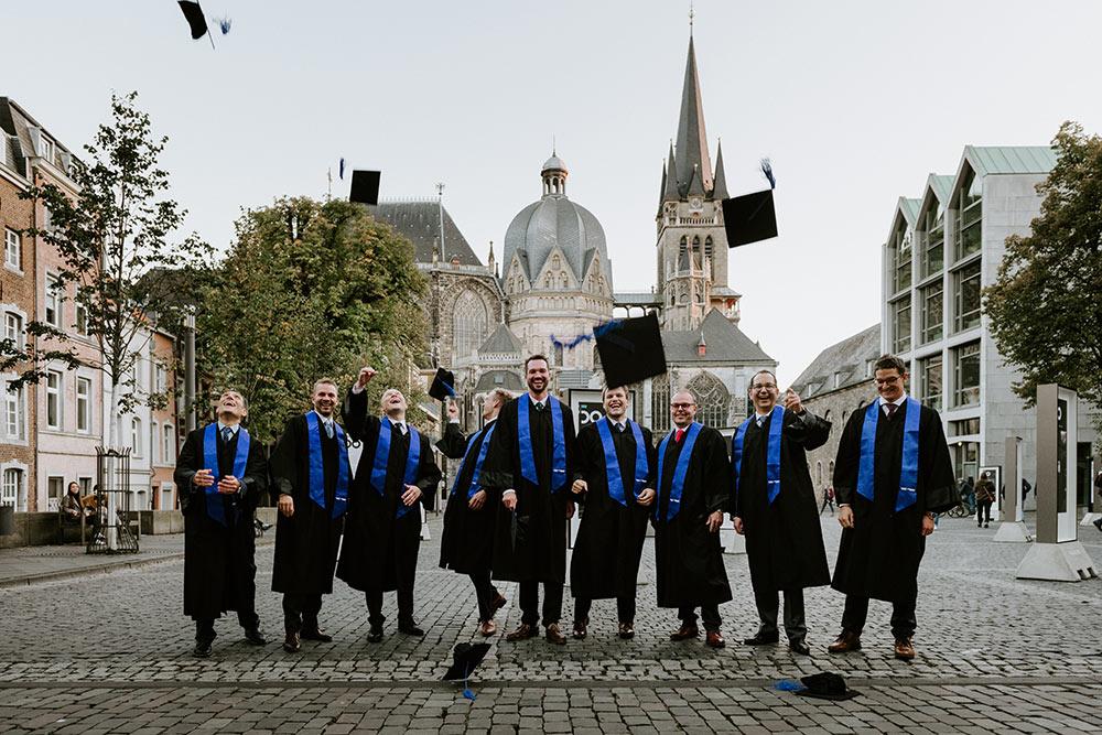 Absolventen des Executive MBA der RWTH Business School beim Hüte werfen vor dem Aachener Dom.